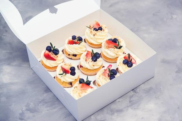 Set di diversi deliziosi cupcakes. scatola di carta con cupcakes alla frutta. cupcakes vacanza con fragole e mirtilli.