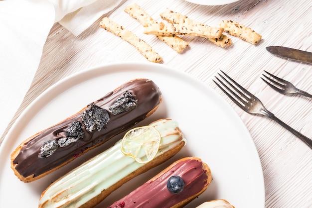 Set di diversi dolci eclair sul tavolo di legno