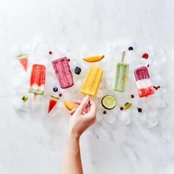 Un insieme di diversi frullati di bacche congelate per lecca-lecca su un bastone con anni e frutti. la mano della ragazza prende un frullato su un bastoncino dai cubetti di ghiaccio. lay piatto