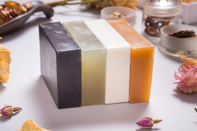 Insieme di briks di sapone fatti a mano del latte differente su fondo grigio