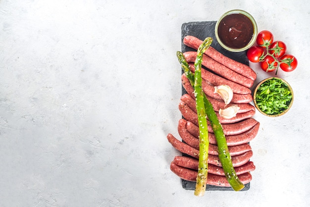 Set di diverse salsicce di carne cruda di manzo, maiale e pollo sul tavolo da cucina con spezie, salse e verdure per grigliare.
