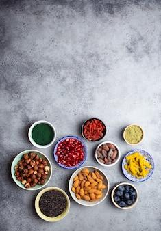 Set di diversi supercibi in ciotole su sfondo grigio pietra: spirulina, bacche di goji, cacao, tè verde matcha, quinoa, semi di chia, mirtilli, noci per una vita felice e sana, vista dall'alto, spazio copia