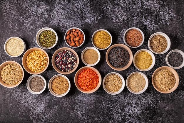 Set di diversi supercibi: cereali integrali, fagioli e legumi, semi e noci, vista dall'alto.