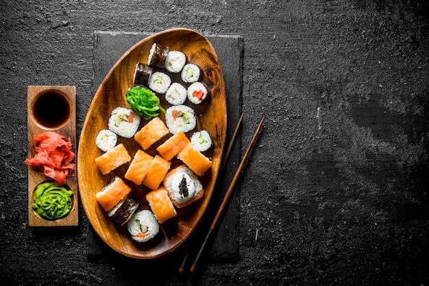 Set di diversi rotoli di sushi con zenzero, salsa di soia e wasabi sul tavolo rustico nero