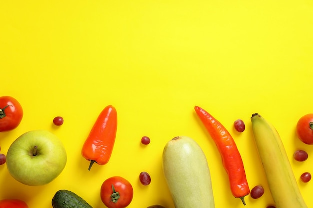 Set di diverse verdure e frutta su sfondo giallo