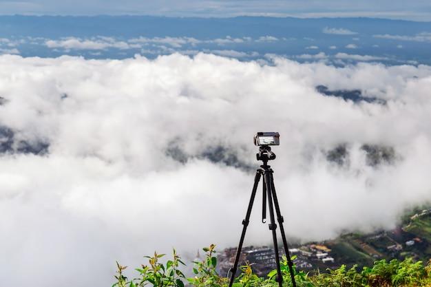 Posiziona una fotocamera digitale su un treppiede per catturare la vista del cielo, delle nuvole e delle montagne