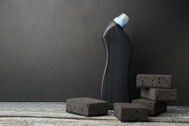 Set di spugne per lavare i piatti e una bottiglia di plastica su una tavola nera