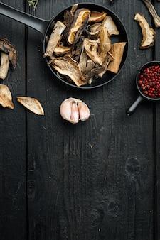 Set di funghi secchi in padella in ghisa, sul tavolo in legno nero tavolo, vista dall'alto laici, copyspace
