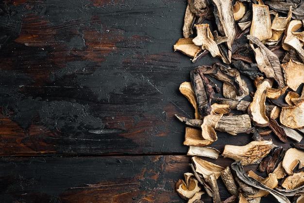 Set di funghi secchi impostati, sul vecchio fondo di tavola in legno scuro, vista dall'alto piatto laici,