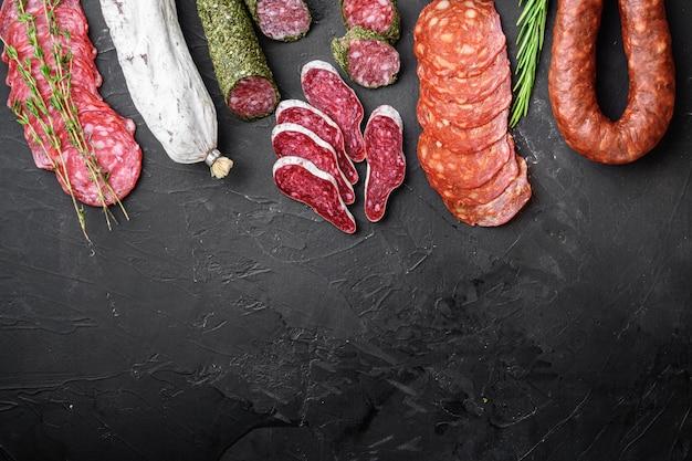 Set di salame stagionato, salsicce spagnole, fette e tagli su sfondo nero, piatto con spazio di copia.