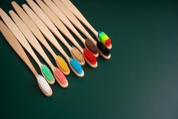 Un set di spazzolini da denti antibatterici ecologici in legno di bambù su una superficie verde scuro