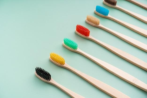 Un set di spazzolini da denti antibatterici ecologici in legno di bambù su una superficie verde chiaro