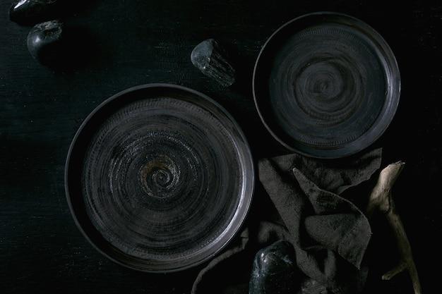 Set di piatti vuoti in ceramica nera con pietre nere e legno intorno su tovagliolo in tessuto su fondo di legno nero. disposizione piatta.