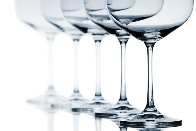 Set di bicchieri di vino vuoti su sfondo bianco.