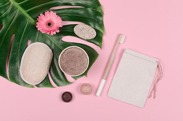 Set di cura quotidiana di prodotti ecologici su foglia di monstera tropicale. zero sprechi