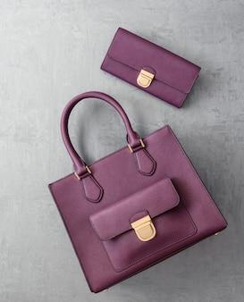Set di borse da donna alla moda su superficie intonacata grigia, vista dall'alto