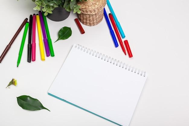 Set di pennarelli in diversi colori e un quaderno bianco