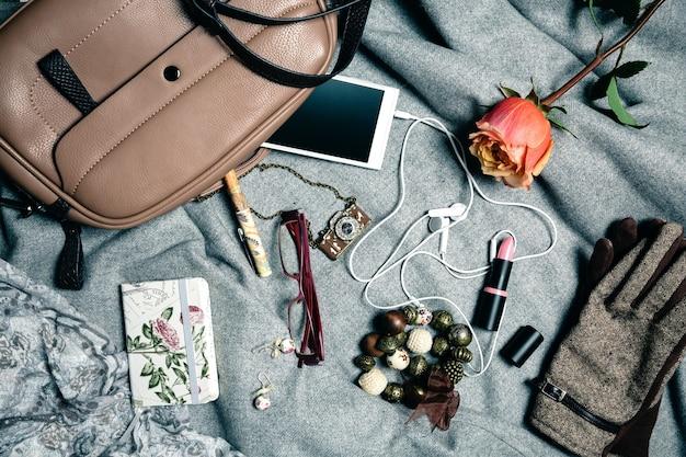 Set di accessori femminili da borsetta su sfondo grigio. vista dall'alto.