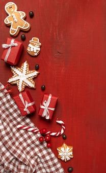 Impostare biscotti festivi di capodanno, regali e fiocco di neve su legno rosso