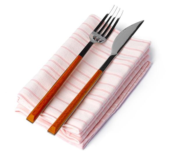 Set di forchetta e coltello su un asciugamano. isolato su sfondo bianco. vista dall'alto.