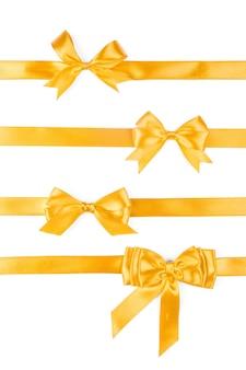 Un insieme di quattro archi del regalo del nastro dorato isolati su bianco