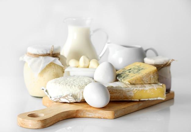 Set di latticini freschi su tavola di legno, su bianco