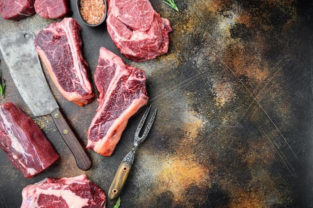 Set di bistecche di manzo marmorizzate crude fresche, tomahawk, t bone, club steak, rib eye e tagli di filetto, su vecchio rustico scuro