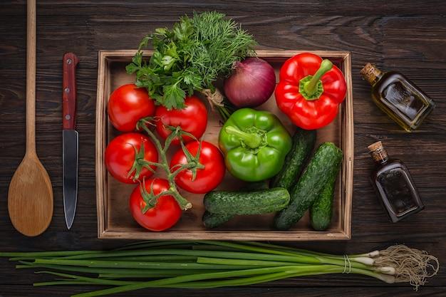 Set di insalate fresche. verdure fresche in cassetta di legno, una bottiglia di olio d'oliva e aceto balsamico