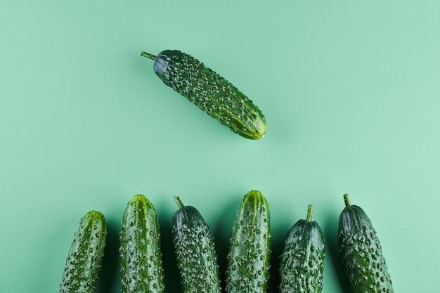 Set di cetrioli freschi interi su uno sfondo verde, modello alimentare. disegno dello sfondo della carta da parati del cetriolo del giardino