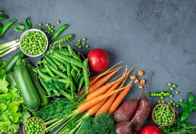 Un insieme di verdure fresche e giovani su uno sfondo blu scuro. vista dall'alto, copia dello spazio.
