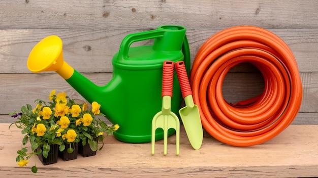 Set da strumenti verdi e arancioni, viola fiori gialli, tubo per irrigazione e piccoli attrezzi da giardinaggio a mano stanno su fondo in legno. copia spazio. largo. avvicinamento