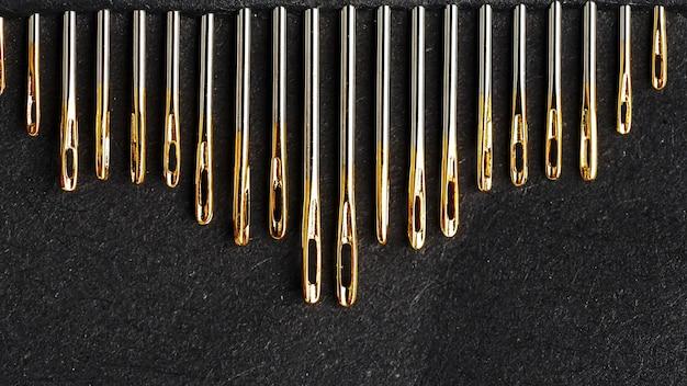 Set di aghi d'oro su uno sfondo nero di fila.