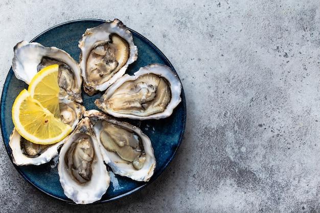 Set di mezza dozzina di ostriche fresche aperte in guscio con spicchi di limone servite su piatto rustico blu su sfondo grigio pietra, primo piano, vista dall'alto, spazio per il testo