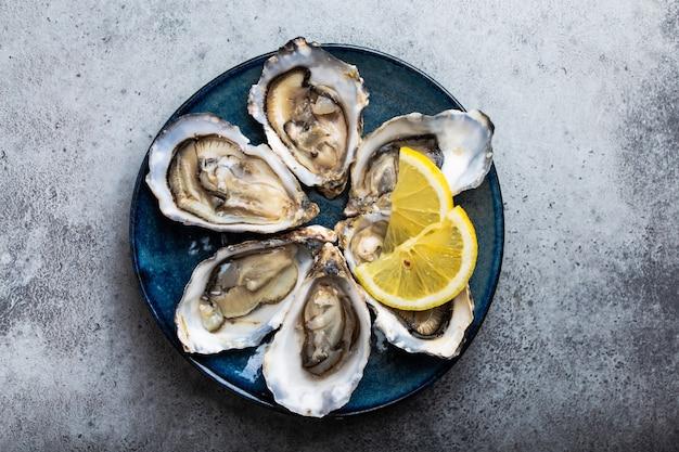 Set di mezza dozzina di ostriche fresche aperte in guscio con spicchi di limone servite su piatto rustico blu su sfondo grigio pietra, primo piano, vista dall'alto Foto Premium