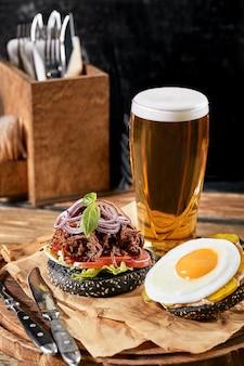 Set di hamburger con uova e birra. un set standard di bevande e cibo nel pub, birra e snack.