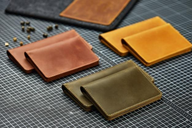 Set di articoli in pelle fatti a mano, portachiavi, portafoglio, borsa, blocco note, manuale. pelletteria artigianale, primo piano.