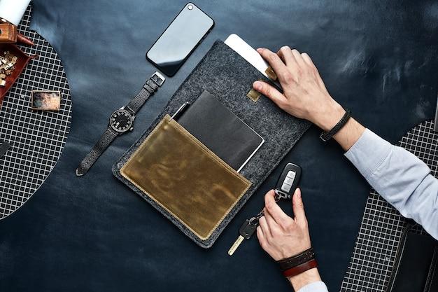 Set di articoli in pelle fatti a mano in mani maschili, portachiavi, portafoglio, borsa, blocco note, manuale. pelletteria artigianale, primo piano.