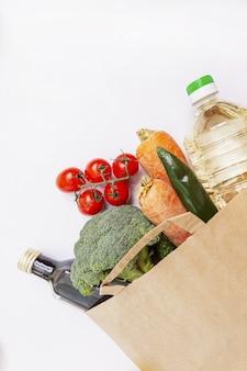 Set di prodotti sani in un sacchetto di carta ecologico su uno sfondo bianco.