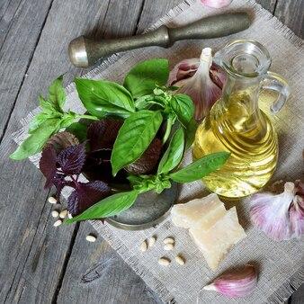Set di erbe, spezie e altri prodotti per la preparazione del pesto italiano su fondo di legno scuro