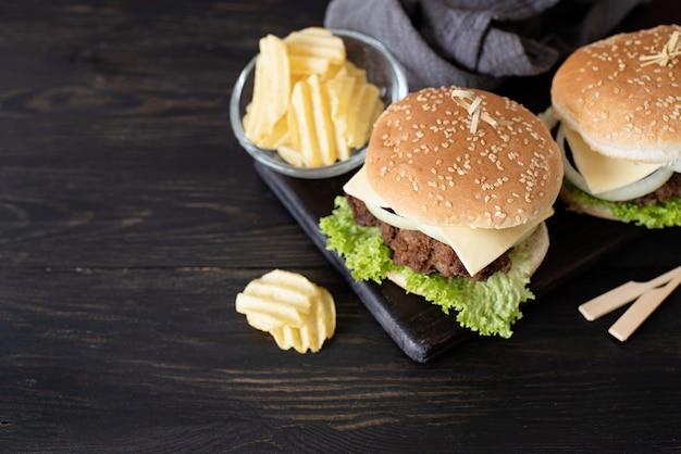 Un set di deliziosi hamburger fatti in casa di formaggio di cipolla di manzo e lattuga su uno sfondo di legno scuro