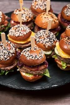 Set di deliziosi hamburger fatti in casa a base di carne di manzo, pancetta, formaggio, insalata e pomodori su uno sfondo scuro di cemento. cibo spazzatura grasso da vicino. con copia spazio. modello di fast food.