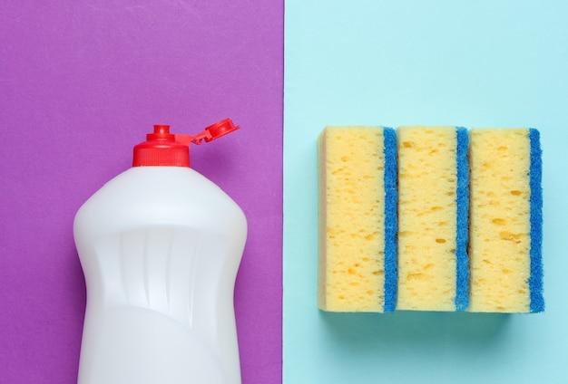 Set di casalinghe per lavare i piatti. lavastoviglie. bottiglia di utensili per il lavaggio, spugne su sfondo blu viola. vista dall'alto.