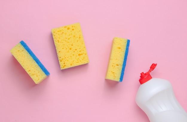 Set di casalinghe per lavare i piatti. lavastoviglie. bottiglia di utensili per il lavaggio, spugne su sfondo rosa. vista dall'alto.