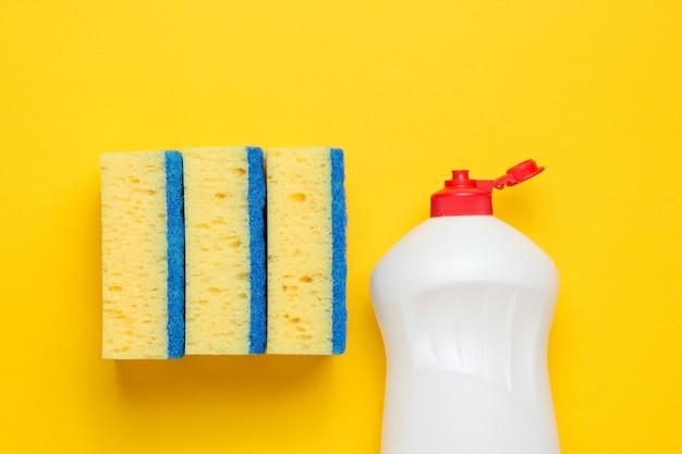 Set di casalinghe per lavare i piatti. lavastoviglie. bottiglia di utensili di lavaggio, spugne su sfondo giallo. vista dall'alto.