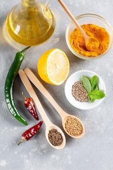Set di ingredienti per cucinare cibo indiano spezie ed erbe aromatiche assortite indiane tradizionali curry cardamomo aglio pepe foglie di curry olio peperoncino peperoni limone preparazione pasto esotico vista dall'alto