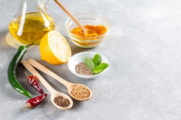 Set di ingredienti da cucina cibo indiano tradizionale indiano assortiti spezie ed erbe aromatiche curry cardamomo aglio pepe foglie di curry olio peperoncino peperoni limone vista dall'alto con lo spazio della copia