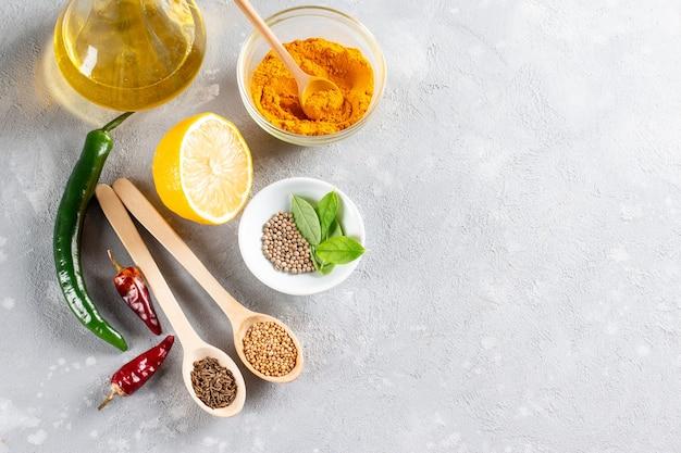 Set di ingredienti per cucinare cibo indiano tradizionale indiano assortiti spezie ed erbe aromatiche curry curcuma cardamomo aglio pepe foglie di curry olio peperoncino limone vista dall'alto con lo spazio della copia