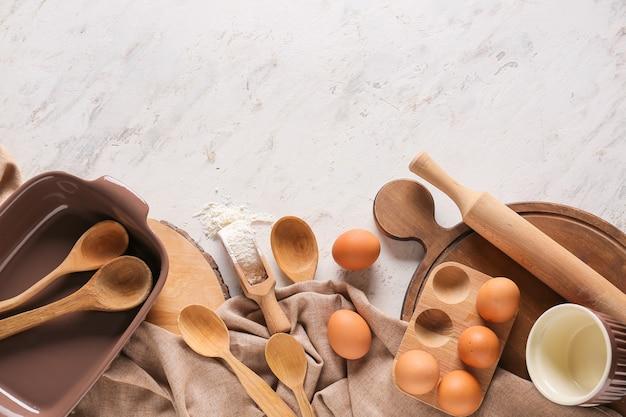 Set di utensili da cucina e ingredienti per la preparazione di prodotti da forno su sfondo chiaro