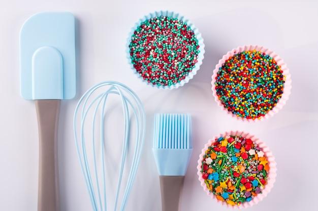 Set di stoviglie per cucinare pasticcini e spruzzi di arcobaleno per la decorazione su sfondo bianco