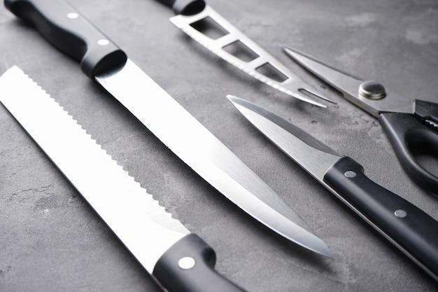 Un set di coltelli. vari utensili della cucina sulla tavola grigia, primo piano.